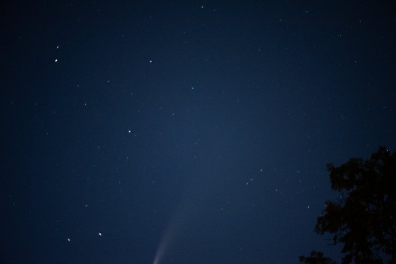 The night sky with a comet tail barely visible at the bottom of the photo.
