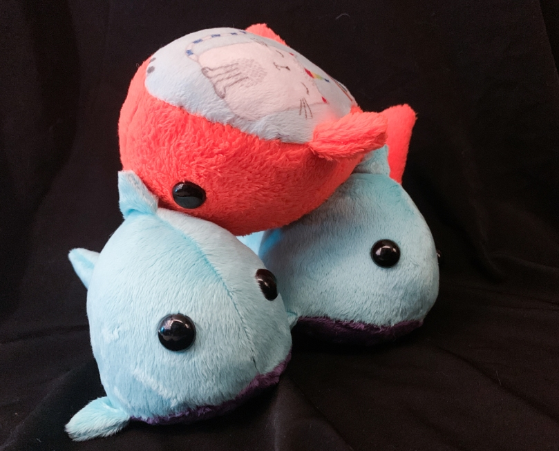 three stuffed sharks, two are blue with purple bellies and one is orange with a cat on its belly. The orange one is upside down on top of the other two, which are right side up.
