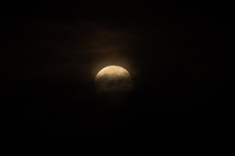 Moon still emerging from behind clouds